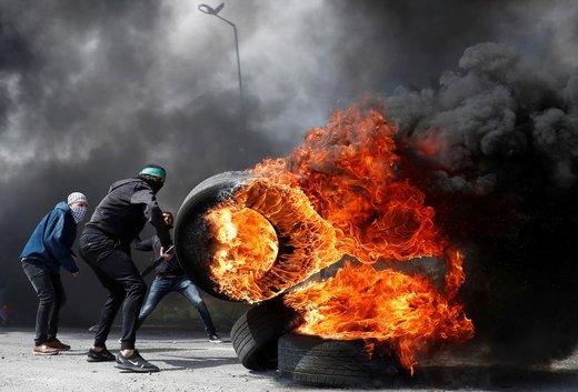 یک معترض فلسطینی به هنگام برخورد با نیروهای اسرائیلی در نزدیکی محل سکونت یهودیان، لاستیک مشتعل را حرکت میدهد