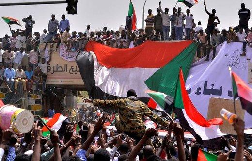 بعد از اینکه عمرالبشیر، رئیسجمهور سودان، توسط نیروهای امنیتی بازداشت شد، یک افسر ارتشی در میان جمعیت در خارطوم، پرچم ملی کشورش را به دست گرفته است
