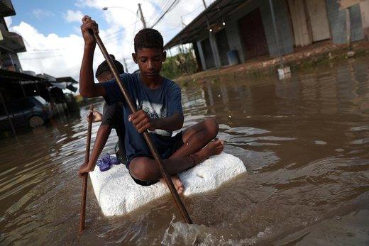 بچهها با سوار شدن بر روی یک جسم بر روی سیلابها در شهر ریودوژانیرو  برزیل حرکت میکنند