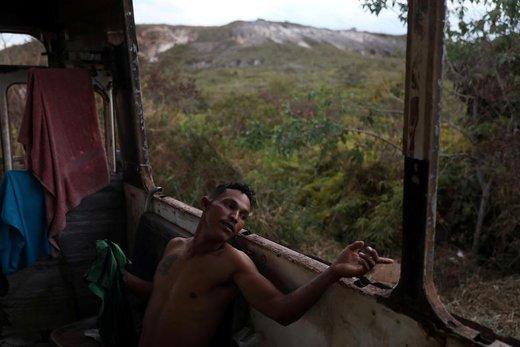 یک مهاجر ونزوئلایی در اتوبوس متروکه ای در شهر مرزي Pacaraima، برزيل استراحت می کند. او پیش از این در یک خودروی مرسدس بنز متروکه به مدت 3 ماه زندگی کرده است.