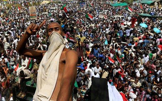 یک معترض سودانی در شهر خارطوم پشت کامیون ارتش سوار شده و تاکید دارد که عمر البشیر، رئیسجمهور برکنار شده این کشور، باید جایگرین شورای نظامی ارتش شود