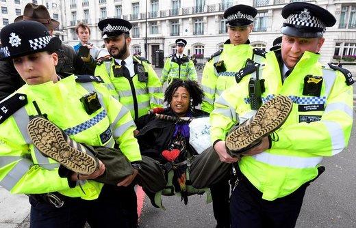 """افسران پلیس یک معترض را در اعتراضات گروه """"شورش علیه انقراض"""" در لندن حمل می کنند، این گروه به سیاستهای دولتی درباره تغییرات اقلیمی معترض است"""