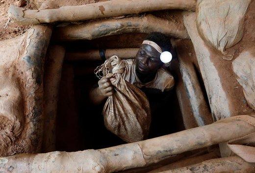 یک معدنچی حامل کیسه سنگ از داخل گودالی در غنا بالا میآید