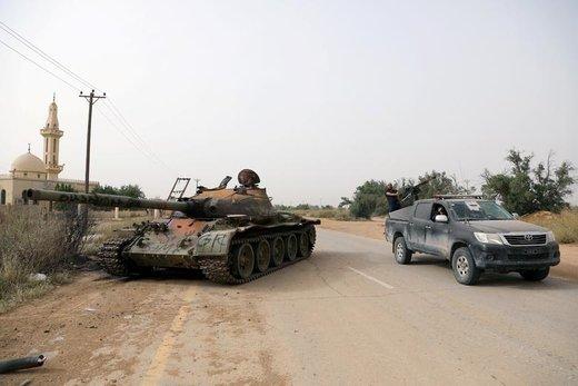 عبور اعضای نیروهای دولتی لیبی از نزدیکی یک مخزن آسیب دیده در جنوب غربی طرابلس که متعلق به نیروهای شرقی است