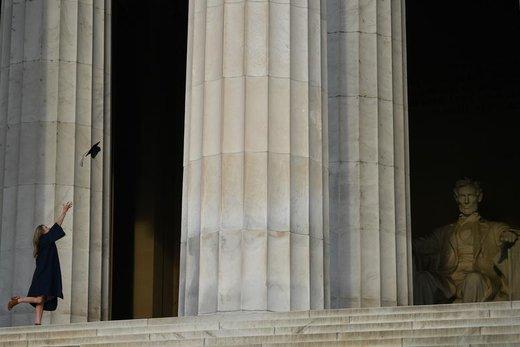 یک زن کلاه فارغالتحصیلی خود را در مقابل یادبود لینکلن در شهر واشنگتن دی سی آمریکا به هوا پرتاب کرده است