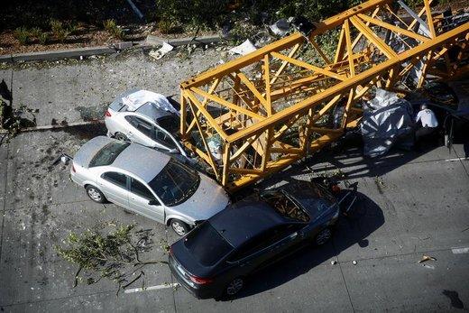 افسر پلیس شهر سیاتل آمریکا خودروهایی که در اثر سقوط جرثقیل بر روی آنها آسیب دیده اند را بررسی میکند، این حادثه 4 قربانی گرفت