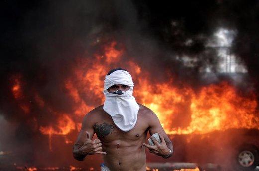 یک تظاهر کننده مخالف دولت ونزوئلا  در حالی که زخمی شده و سنگی در دست دارد، در مقابل یک اتوبوس در حال سوختن در نزدیکی پایگاه هوایی در شهر کاراکاس ایستاده است