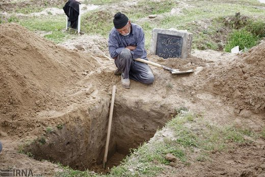 تشلی بکه 65 ساله، در حال استراحت کنار قبری است که برای مراسم تدفین در قبرستان قوشتپه شهر آققلا آماده کرده است