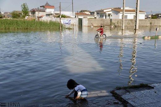 کودکان در حال بازی و دوچرخه سواری در سیلاب یکی از خیابانهای شهر آققلا هستد