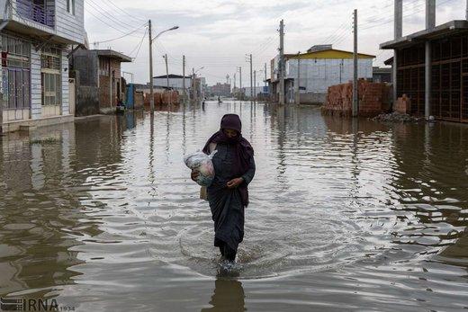زنی در حال عبور از میان سیلاب در یکی از خیابانهای شهر آققلا است