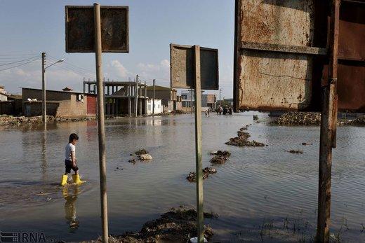 محمد قئزل 6 ساله در حال راه رفتن و عبور میان سیلاب در شهر آققلا است