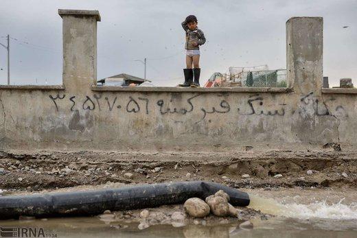 محمد یاسین کم 4 ساله، بر روی دیوار قبرستان قوش تپه در شهر آق قلا ایستاده است