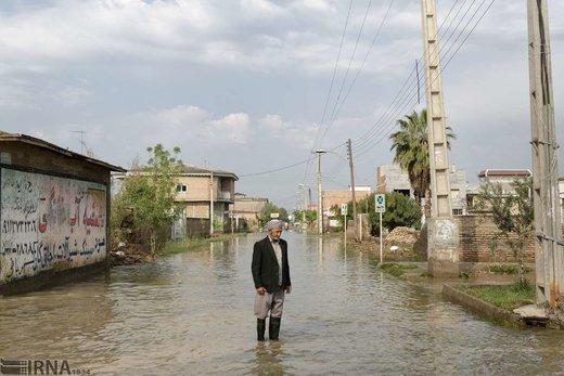 پیرمرد ترکمن جهت حمل و نقل در خیابانهای سیلاب گرفته، برای سوار شدن به تراکتور ایستاده است