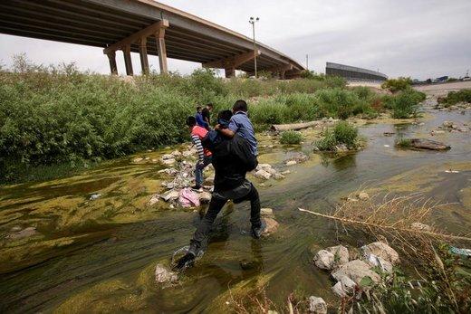 مهاجران در حال عبور از رودخانه Bravo که در خط مرزی میان شهر الپاسو ایالت تگزاس آمریکا و شهر سیوداد خوارس مکزیک قرار دارد