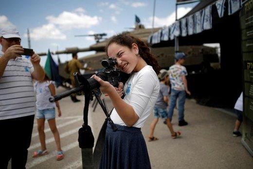 یک دختر در مراسم یادبود سربازان در اسرائیل با تفنگ بازی میکند