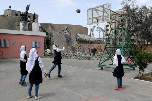 دانشآموزان فلسطینی در داخل مدرسه آسیب دیده خود، در نزدیکی یک ساختمان که در حملات هوایی اسرائیل تخریب شده بود، در شهر غزه بسکتبال بازی می کنند