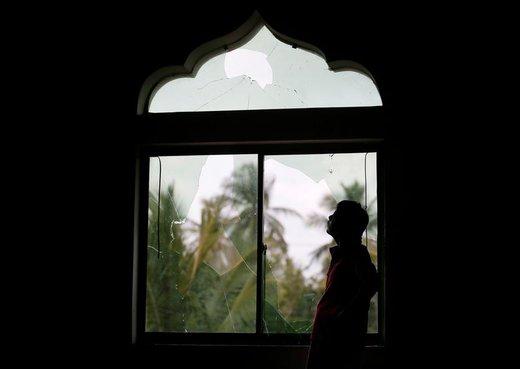 یک مرد مسلمان به پنجرههای شکسته مسجدی در سریلانکا، پس از حمله به آنجا نگاه میکند