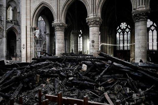 یک کارگر بر روی داربست در کلیسای  نوتردام پاریس، یک ماه پس از وقوع آتش سوزی ایستاده است