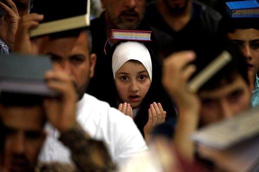 یک دختر شیعه عراقی  در ماه مبارک رمضان در حرم امام علی(ع) شهر نجف عراق، قرآن کریم را بر روی سر خود قرار داده است