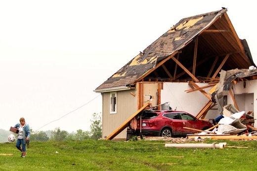 یک  زن پس از وقوع طوفانهای مرگبار در شهر لینوود ایالت کانزاس آمریکا از کنار یک خانه آسیبدیده عبور میکند