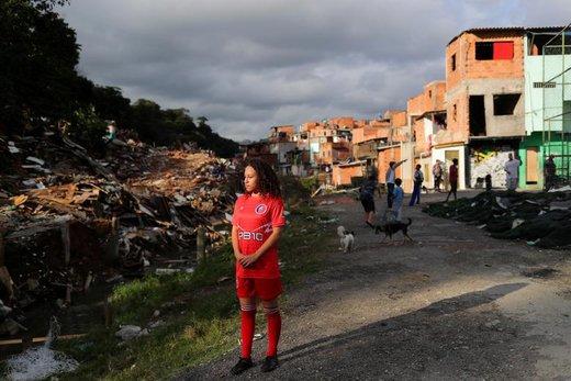 یک دختر 14 ساله منتظر گرفتن توپ از یک پسربجه در زمان تمرین فوتبال در حومه شهر سائو پائولو برزیل است