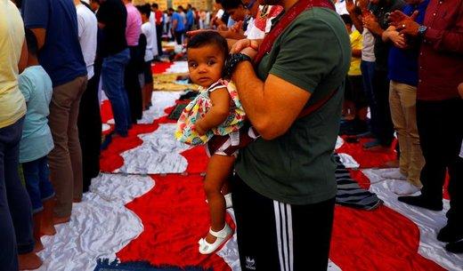 یک کودک در اغوش پدرش به هنگام اقامه نماز عید فطر در شهر قاهره مصر