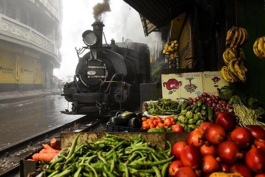 نمایی از عبور قطار راهآهن هیمالیایی دارجیلینگ هند از یک بازار محلی