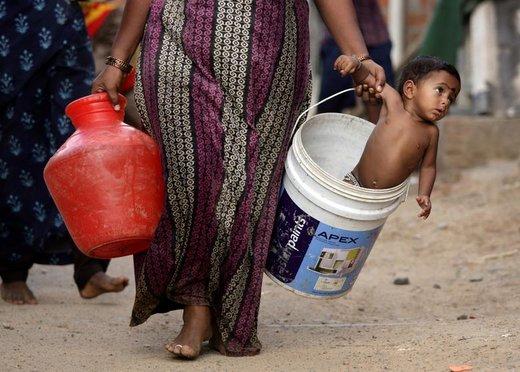 یک زن پس از برداشت آب از تانکر در حومه شهر چنای هند، پسرش رادر یک سطل حمل می کند