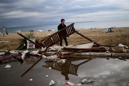 یک مرد پس از طوفان های سنگین در روستای Nea Plagia یونان لوازم شکسته را حمل میکند