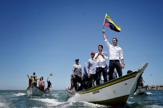 خوان گوایدو، سرکرده مخالفان دولت ونزوئلا، داخل قایقی در نزدیکی جزیره مارگاریتا برای دیدار با طرفدارانش پرچم تکان میدهد