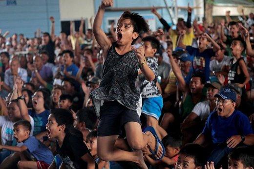 واکنش هواداران مسابقه بوکس در زمان برگزاری مسابقه میان مانی پاکیائو، بوکسور فیلیپینی، با کیث تورمن، بوکسور آمریکایی، در ماریکینا فلیپین