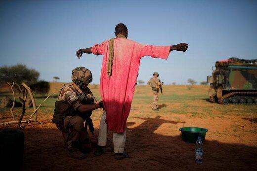 سرباز فرانسوی یک مرد را در  Ndaki مالی بازرسی بدنی میکند