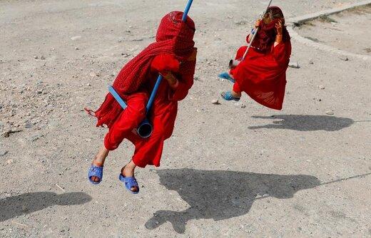 دختران افغانستانی به هنگام تاب بازی در عید قربان صورت خود را پوشاندهاند