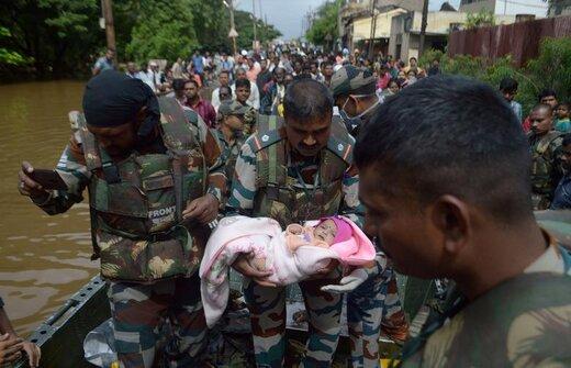 حمل یک نوزاد توسط سرباز در منطقه Sangli هند، تلاش برای نجات شهروندانی که خانههایشان در سیل تخریب شده  و انتقال آنها به مناطق امن ادامه دارد