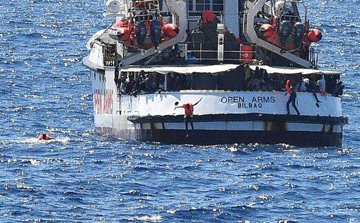 مهاجران در نزدیکی ساحل از کشتی نجات اسپانیایی در لامپدوسا ایتالیا به داخل دریا می پرند