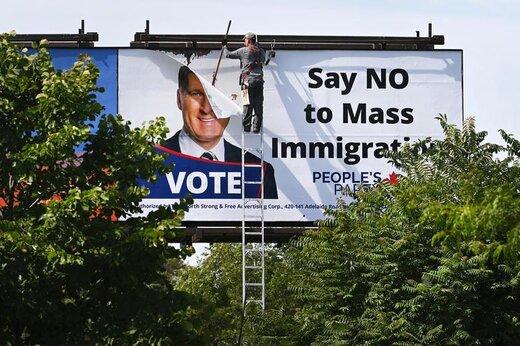 یک کارگر بیلبورد تبلیغاتی ماکسیم برنیر، رهبر حزب مردم کانادا، که شعارش «نه به مهاجران انبوه بگویید» است، را در شهر تورنتو  کانادا بر میچیند