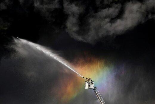 آتش نشانان در حین اطفای حریق در یک ساختمان صنعتی در سنپترزبورگ روسیه  از نردبان استفاده می کنند