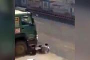 فیلم | موتورسواری که از چرخهای کامیون جان سالم به در برد