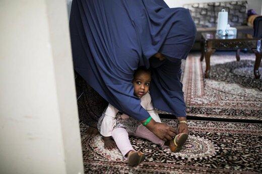 پناهنده سومالیایی در آپارتمانی در شهر کلمبوس ایالت اوهایو آمریکا کفشهای دخترش را به پای او میکند، این پناهنده از سال 2015 درخواستی برای پناهندگی 3 پسر خود از اوگاندا کرده اما پرونده او با سیاستهای دولت ترامپ در عدم پذیرش پناهجویان مواجه شده است