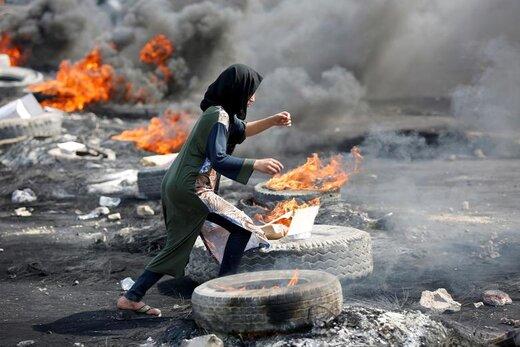دویدن یک تظاهرکننده در جریان تظاهرات ضد دولتی در شهر بغداد عراق از میان لاستیکهای آتشین