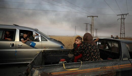 زنی با یک کودک پشت کامیون نشسته و در حال فرار از شهر راسالعین سوریه هستند