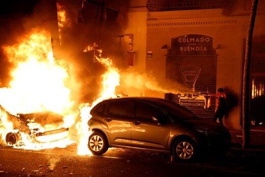 اطفای حریق خودرویی که در اعتراضات در شهر بارسلون اسپانیا آتش زده شده است