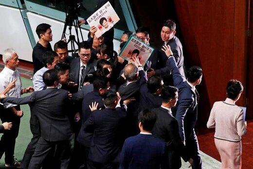 کری لم، رئیس اجرایی هنگ کنک، با اعتراض نمایندگان مخالف خود در پارلمان روبرو و مجبور شد پارلمان این شهر را ترک کند، سخنرانی او از طریق ارتباط ویدیویی از شبکههای تلویزیونی پخش شد