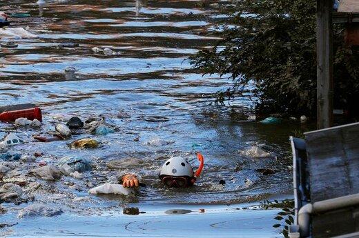 شنای یک امدادگر پس از وقوع طوفان هاگیبیس برای بررسی وضعیت در کاواساکی ژاپن
