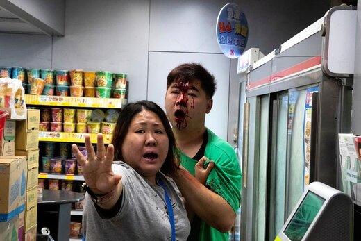 یک زن در تلاش است جلوی معترضین ضد دولتی را در هنگکنگ بگیرد، زیرا آنها به هنگام تظاهرات به یک مرد حمله کرده اند