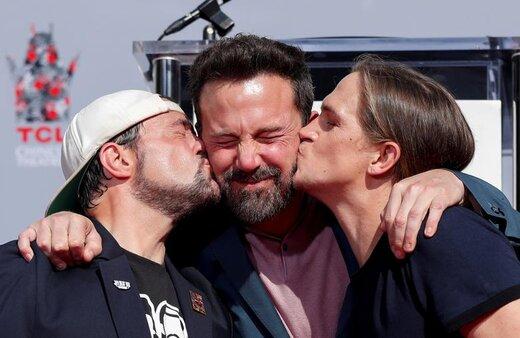 جیسون موس و کوین اسمیت در مراسمی در شهر لسآنجلس آمریکا، بن افلک، هنرپیشه، کارگردان و فیلمنامهنویس آمریکایی، را بوس میکنند
