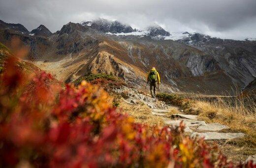 یک کوهنورد در روزهای پاییز در کوههای آلپ در نزدیکی روستایی در اتریش قدم میزند