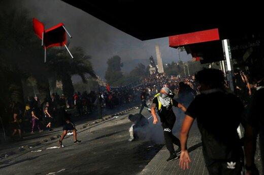 یک معترض به سیاست اقتصادی دولت شیلی در شهر سانتیاگو صندلی پرتاب میکند