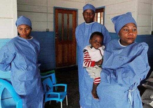 حمل کودک 16 ماههای که مادرش در اثر ابتلا به ابولا جان باخته، در جمهوری دموکراتیک کنگو. زنی که این کودک را در آغوش گرفته، کودکان بازمانده خانوادههای مبتلا به ابولا را سرپرستی میکند