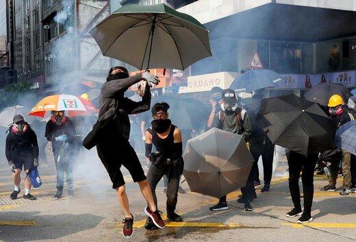 یک تظاهرکننده ضد دولت در راهپیمایی هنگکنگ  قوطی گاز اشکآور را پرتاب میکند